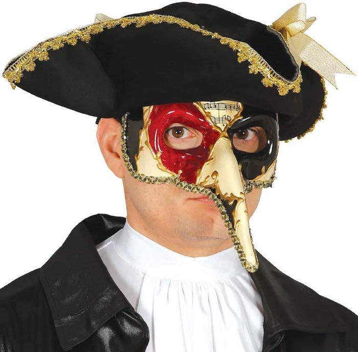 man wearing black hat with gold decorations, masquerade decorations, white mask with red and black paint around the eyes