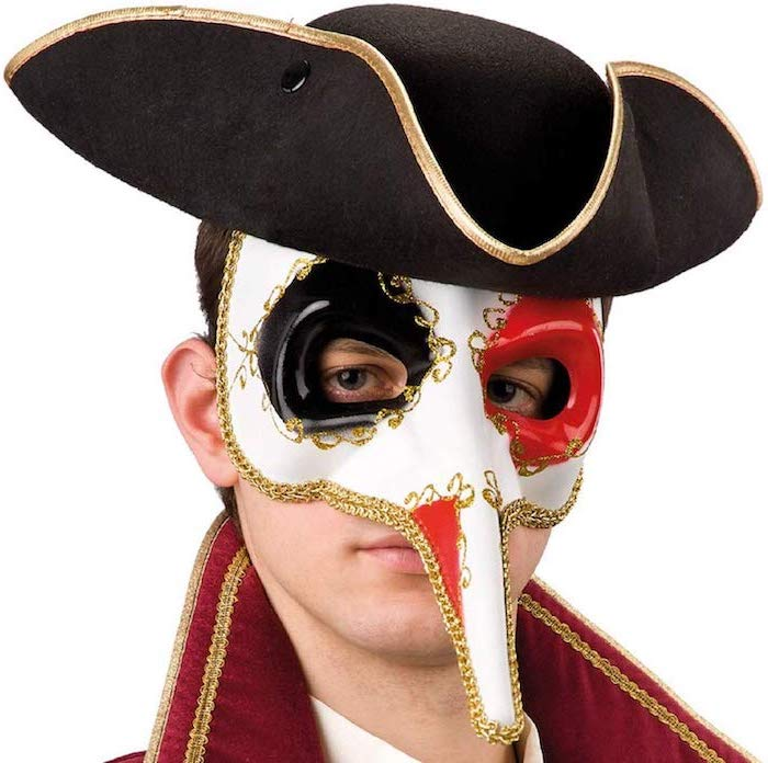 man wearing a black hat, white mask with gold decorations, red and black paint around the eyes, masquerade decorations