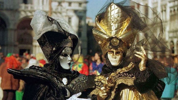 man and woman wearing costumes in black and gold, masquerade decorations, large hats decorated with tulle