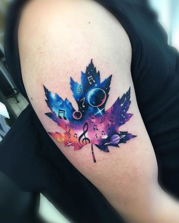 maple leaf with a galaxy inside the frame, space tattoo ideas, musical notes stars and planets, shoulder tattoo