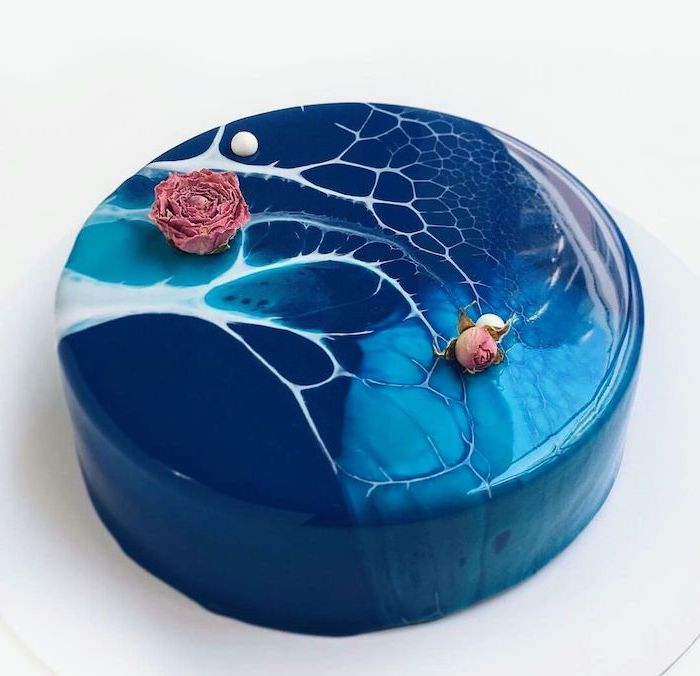 blue and white marble glaze on one tier cake, flower decorations on top, how to make glaze for cake, placed on white tray