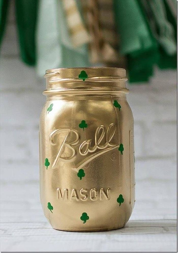 mason jar painted with gold, small green shamrocks painted on it, st patrick's day wreath, placed on white surface