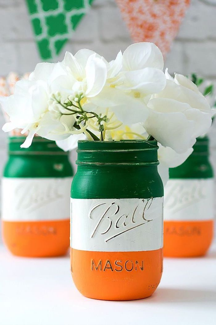mason jars painted in the colors of the irish flag, st patricks decor, green white and orange, white faux flowers inside
