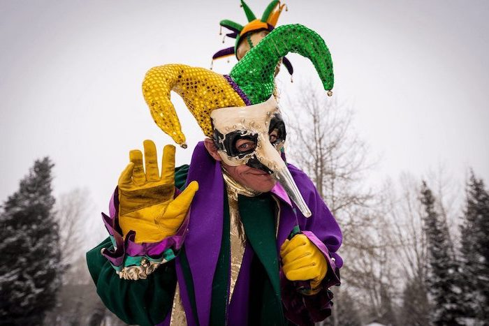 man wearing a purple green and gold costume, jester hat, masquerade masks for women, white mask with long nose