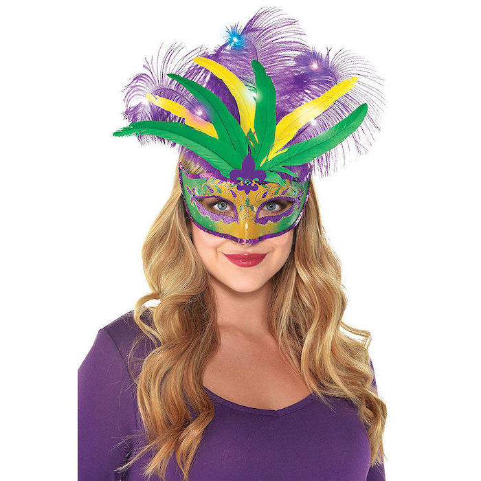 blonde woman, wearing purple blouse, masquerade party masks, gold mask with green and purple decorations and feathers