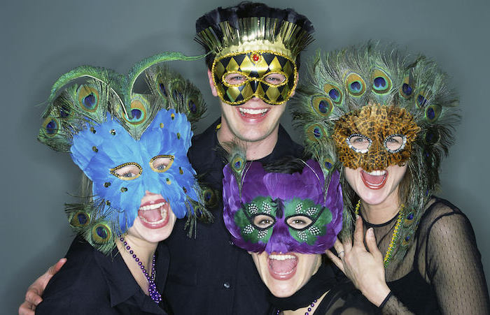 people smiling at the camera, posing for a photograph, what to wear to mardi gras, wearing different masks with feathers