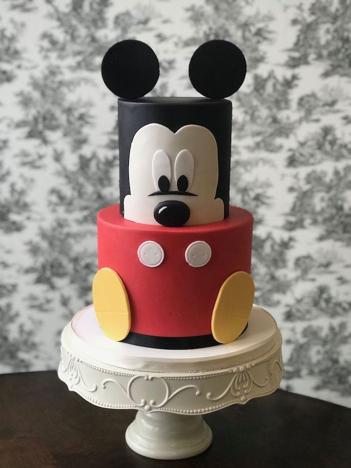 two tier cake, covered with black white and red fondant, mickey mouse cake ideas, placed on white cake stand