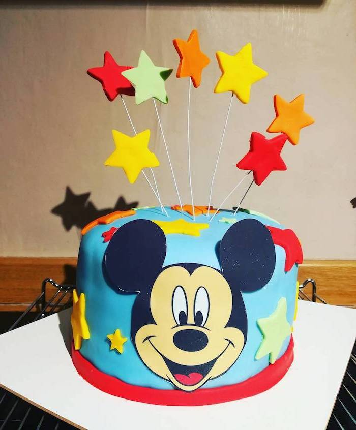 one tier cake, covered with blue fondant, colorful fondant stars cake toppers, mickey mouse cakes 1st birthday