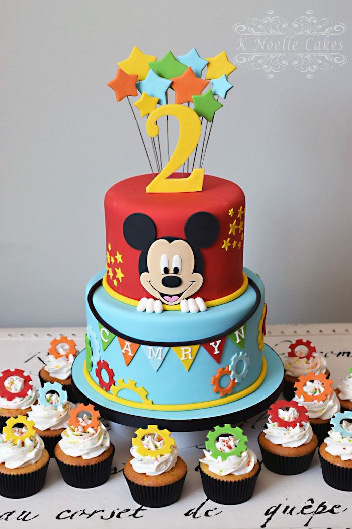 two tier cake, covered with red and blue fondant, mickey mouse cakes 1st birthday, cupcakes arranged around it