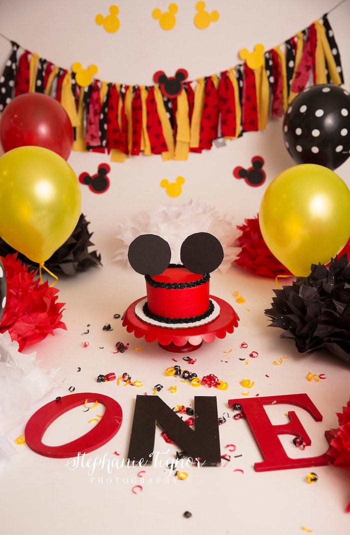 red yellow and black balloons, mickey cake, party decorations, cake in the middle, covered with red fondant