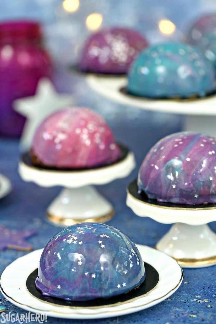 mini galaxy cakes, placed on white cake stands, decorated with white stars sprinkles, how to make glaze for cake