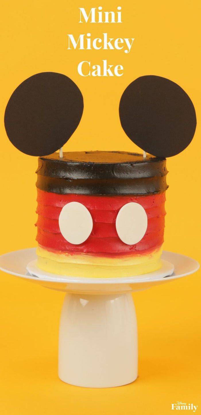 mickey mouse smash cake, mini mickey cake, decorated with brown red and yellow buttercream, placed on white cake stand
