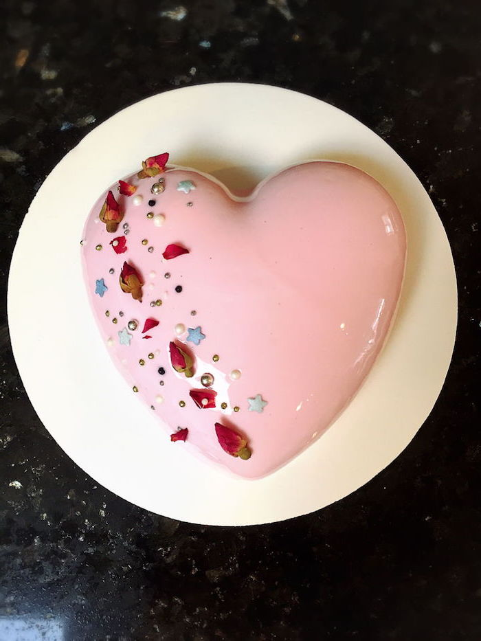 heart shaped one tier cake, covered with pink glaze, flowers and sprinkles on top, mirror glaze cake recipe, placed on white tray