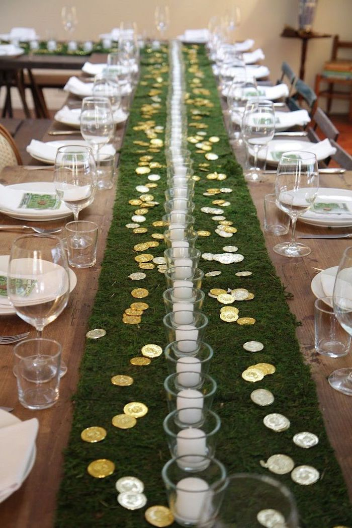 moss table runner, st patricks decor, gold coins scattered on it, around glasses with candles inside, table settings on both sides