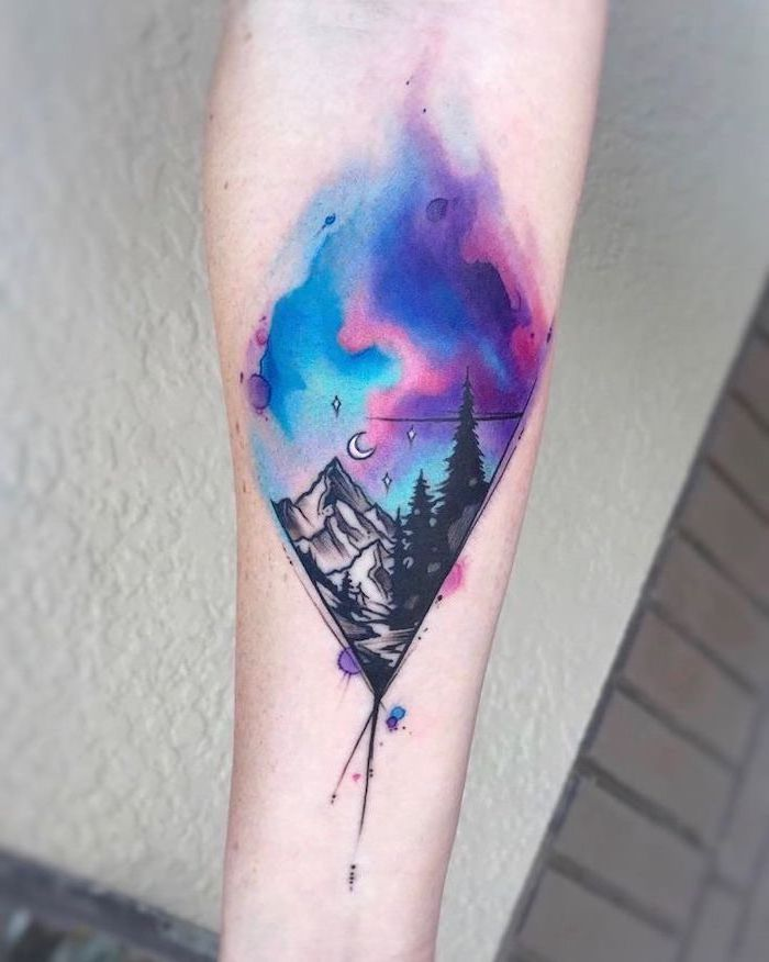 watercolor forearm tattoo, mountain landscape with tall trees, blue pink and purple galaxy above, small space tattoos