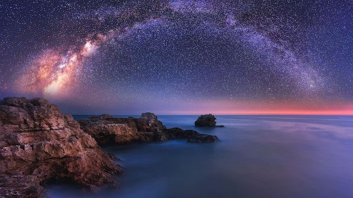 ocean landscape, rocks on the beach next to the water, space wallpaper 4k, galaxy sky filled with stars above the water