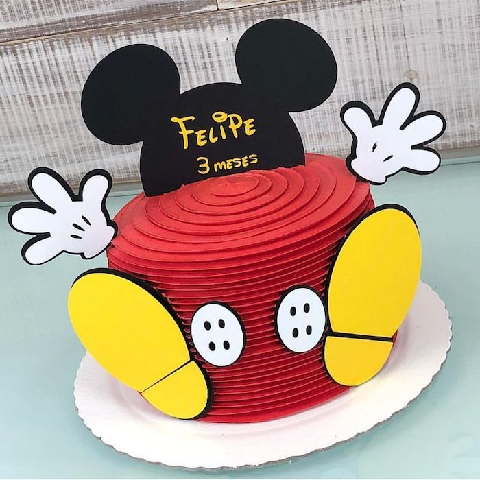 one tier cake, covered with red buttercream, mickey mouse smash cake, placed on white cake tray