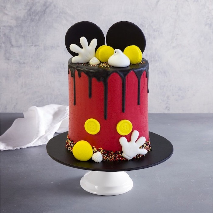 one tier cake, covered with red fondant, chocolate dripping on the sides, mickey mouse smash cake, placed on black cake stand