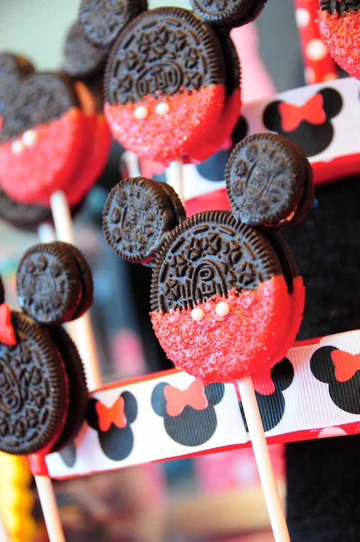 cake pops made of oreos, dipped in red chocolate, mickey mouse smash cake, arranged together on a stand
