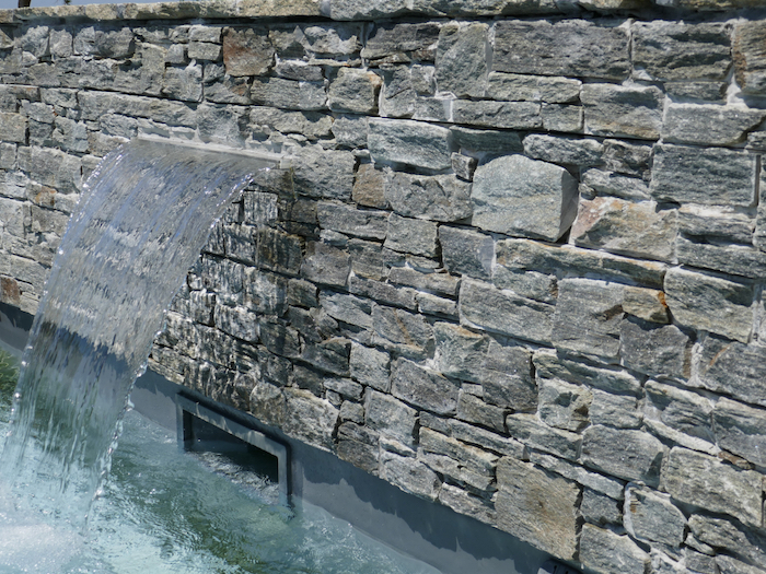 outdoor wall fountain, made with stones, natural stone and reclaimed setts, small pool underneath