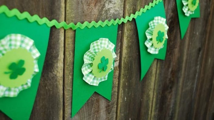 green paper garland with shamrocks, green and white fabric, st patricks decor, hanging on wooden wall