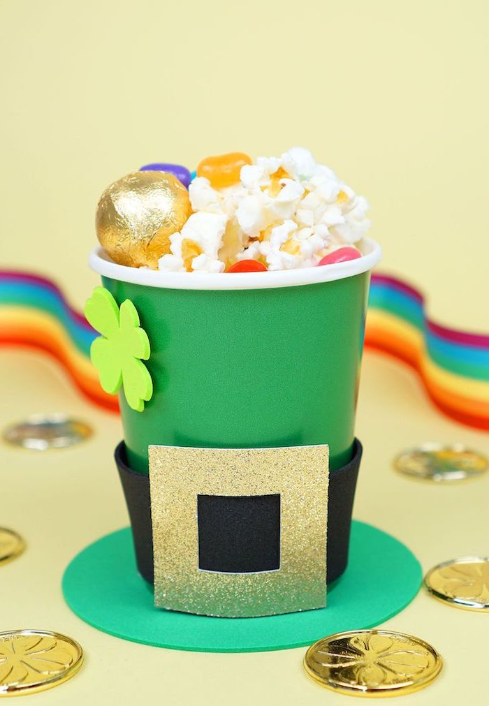 green popcorn bucket, with black and gold belt around it, st patrick's day crafts, gold coins around it