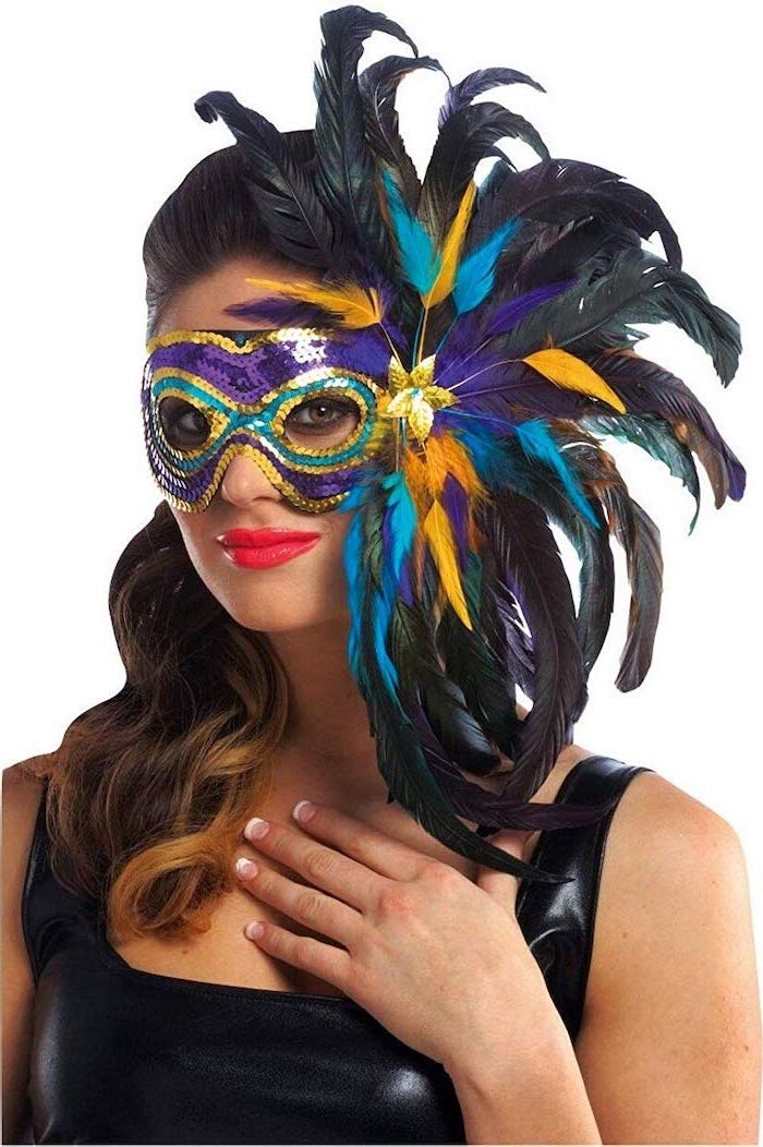 brunette woman wearing black leather top, mask with purple gold green sequins, what to wear to mardi gras, black feathers