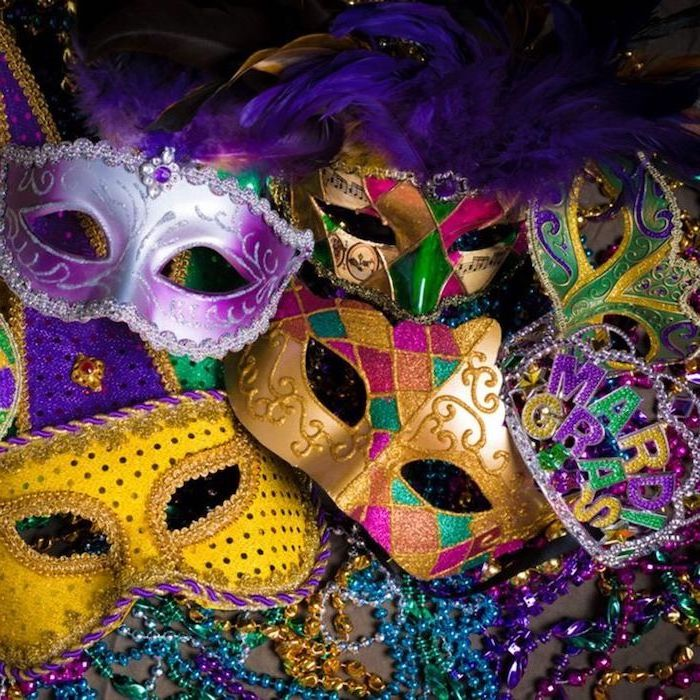 different masks arranged together, placed on surface filled with beads necklaces, what to wear to mardi gras