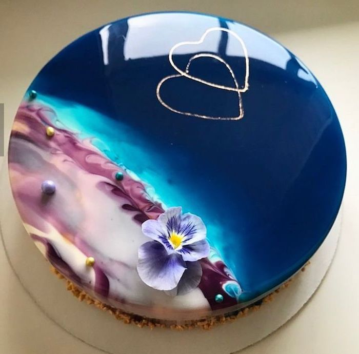 blue and purple glaze on tier cake, glaze icing for cake, flower and hearts decorations on top, placed on white tray