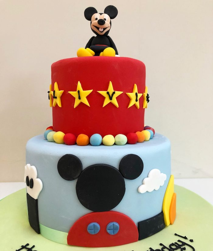 two tier cake, covered with red and blue fondant, mickey mouse cake pops, mickey cake topper