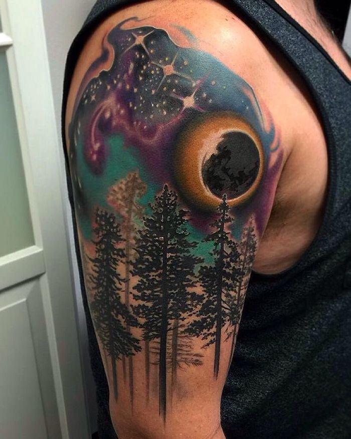shoulder watercolor tattoo, man wearing dark grey top, tall trees with galaxy above them, moon covering the sun, galaxy tattoo small