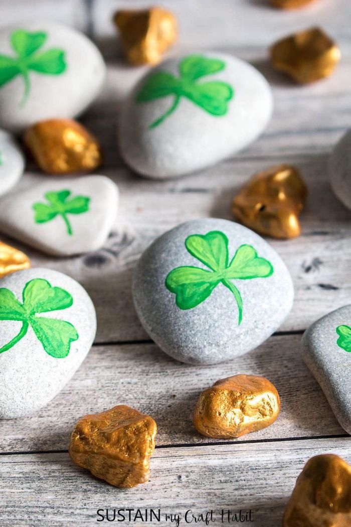 small rocks painted in gold, bigger rocks with green shamrocks painted on them, st patrick's day party ideas