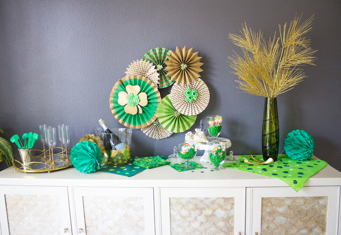table decorated with green and gold napkins, st patricks day games, champagne and glasses, green candy in glass jars