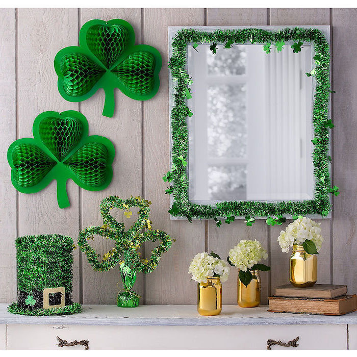 mirror hanging over a cupboard, decorated with green garlands, green paper shamrocks on the wall, st patrick's day decorations