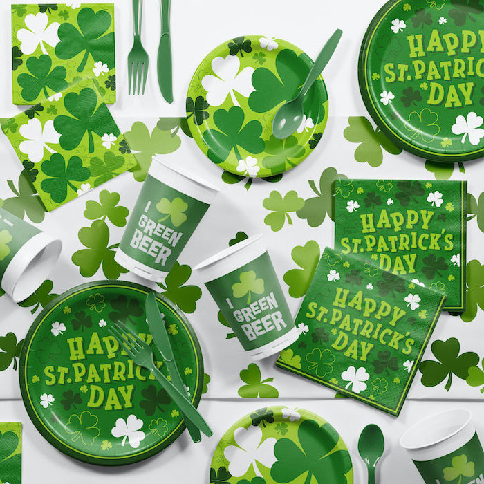 st patrick's day decorations, paper napkins plates cups and utensils, decorated with shamrocks, placed on white table