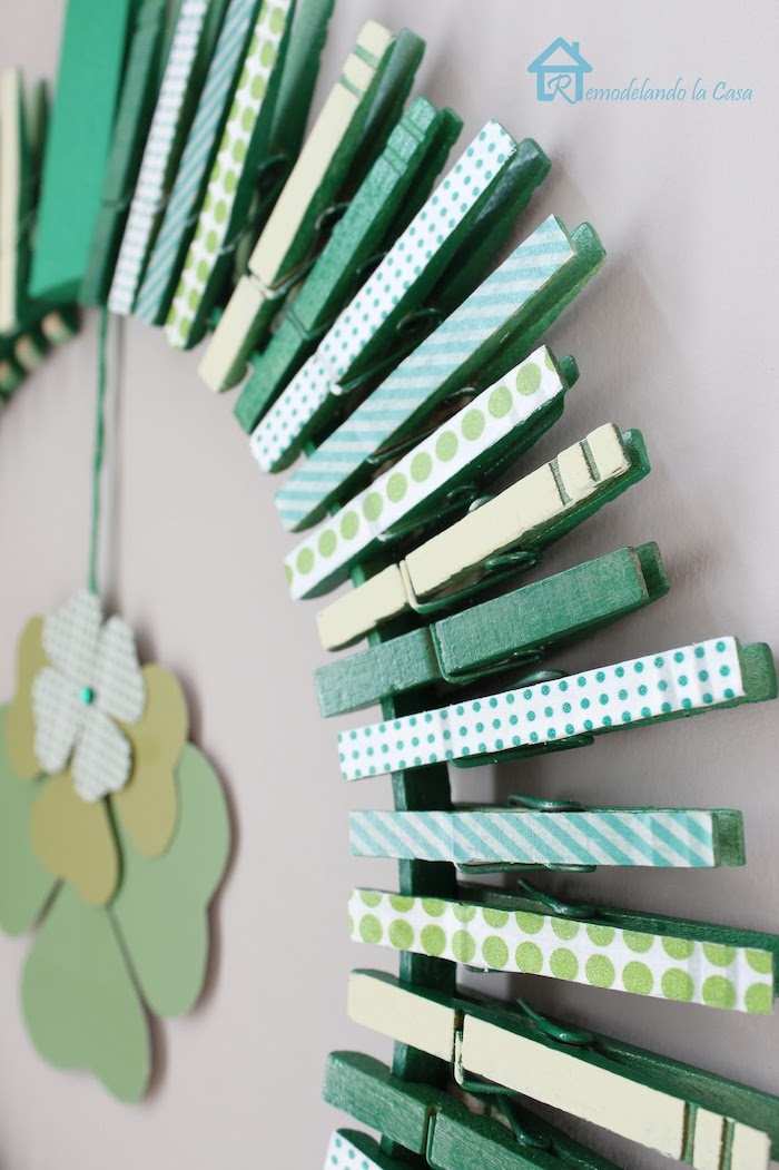 happy st patrick's day, wreath made with clothespins, covered with washi tape with different patterns, hanging on white wall