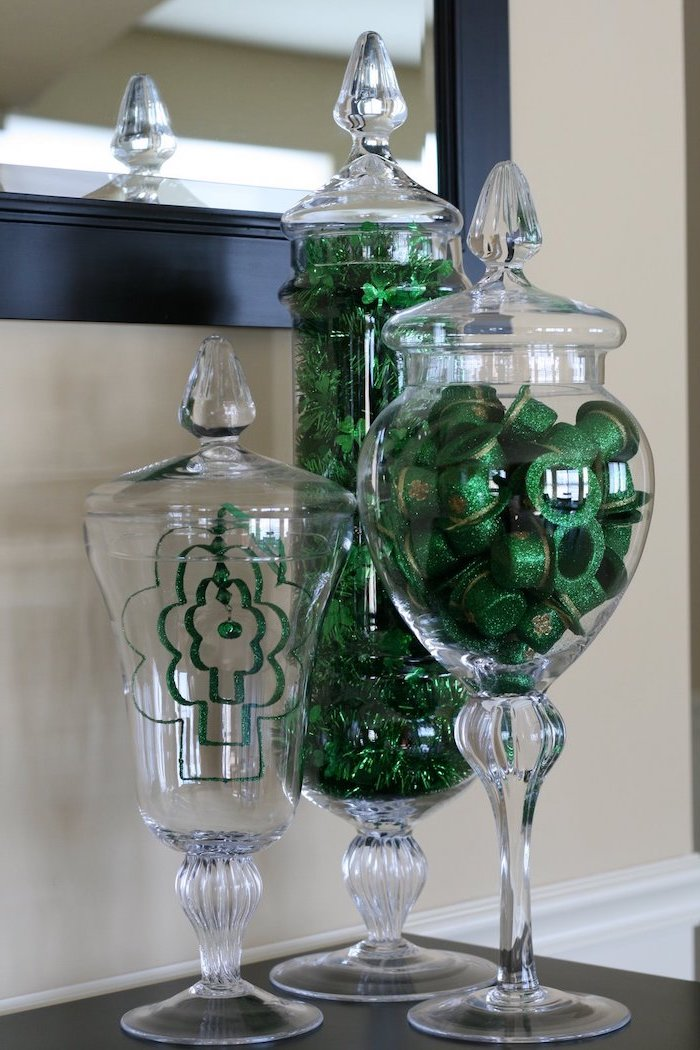 tall glass candy jars, filled with green glitter hats and garlands with shamrocks, st patricks day crafts, placed on black surface