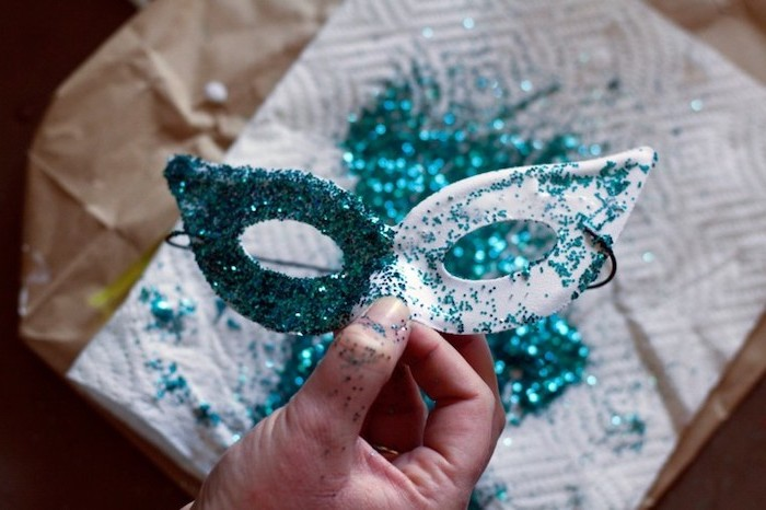 step by step diy tutorial, masquerade masks for couples, white mask covered with turquoise glitter