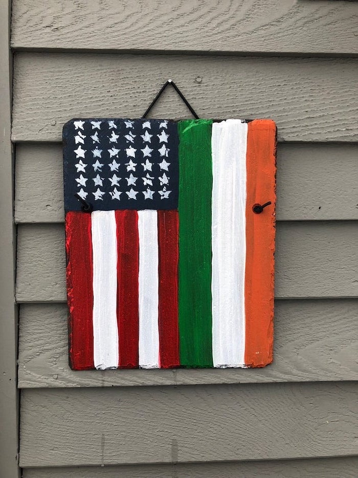 stone board with the usa and irish flags, painted on it, st patricks day games, hanging on grey wooden wall