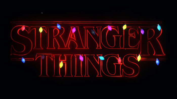 title of the show written in red neon, colorful string lights around it, black background, stranger things wallpaper iphone