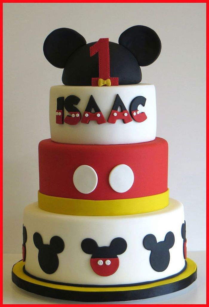 three tier cake, covered with black and white, red and yellow fondant, mickey mouse cake pops, placed on yellow cake tray