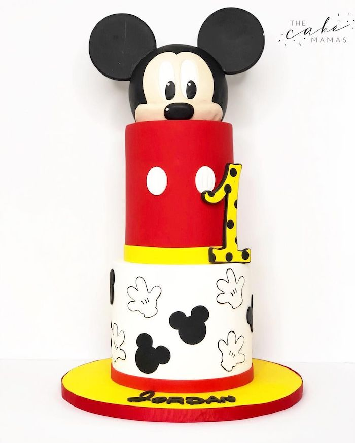 three tier cake, covered with black and white, red and yellow fondant, mickey mouse cake pan, placed on yellow cake tray