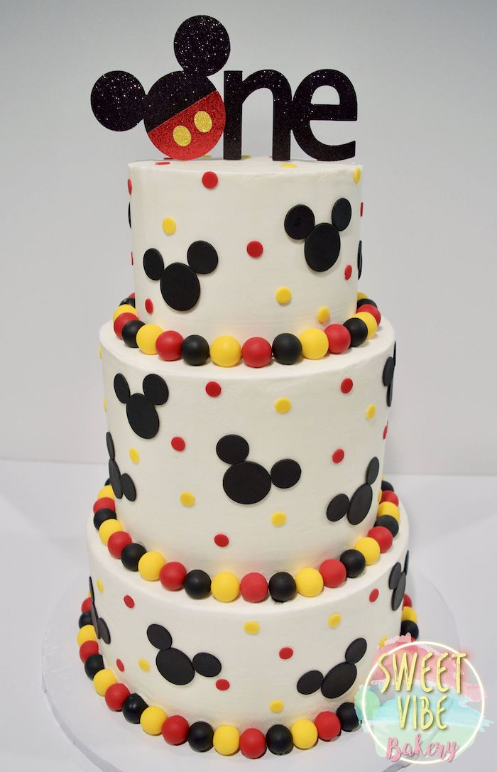 mickey mouse cake pan, three tier cake, covered with white fondant, black red and yellow decorations on it