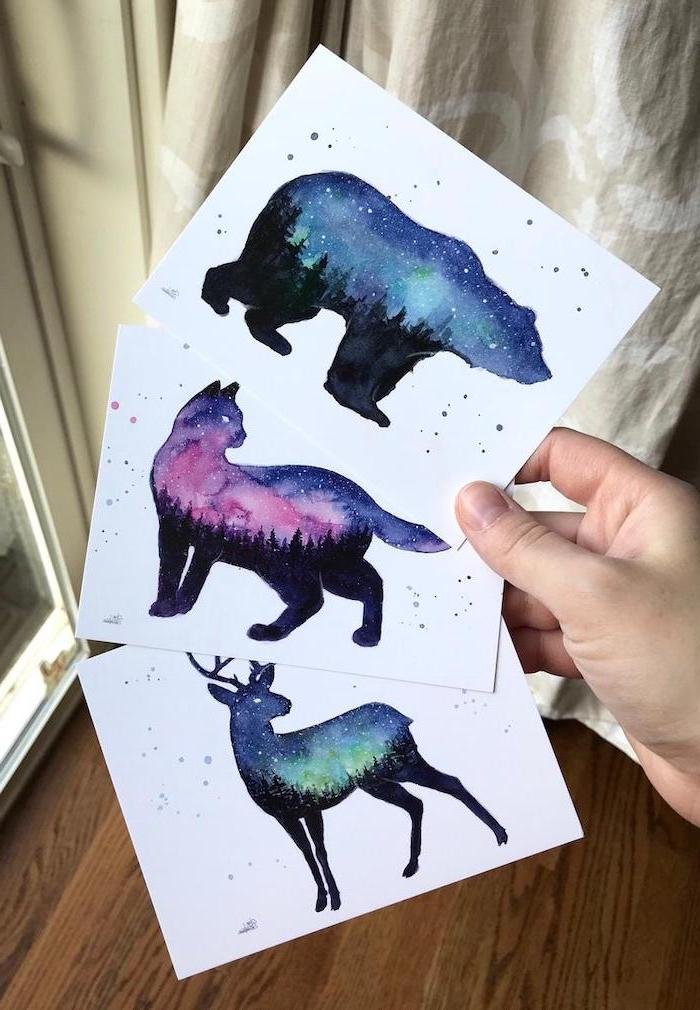 milky way tattoo, three white papers with drawings, bear cat and stag silhouettes, galaxies drawn inside the silhouettes