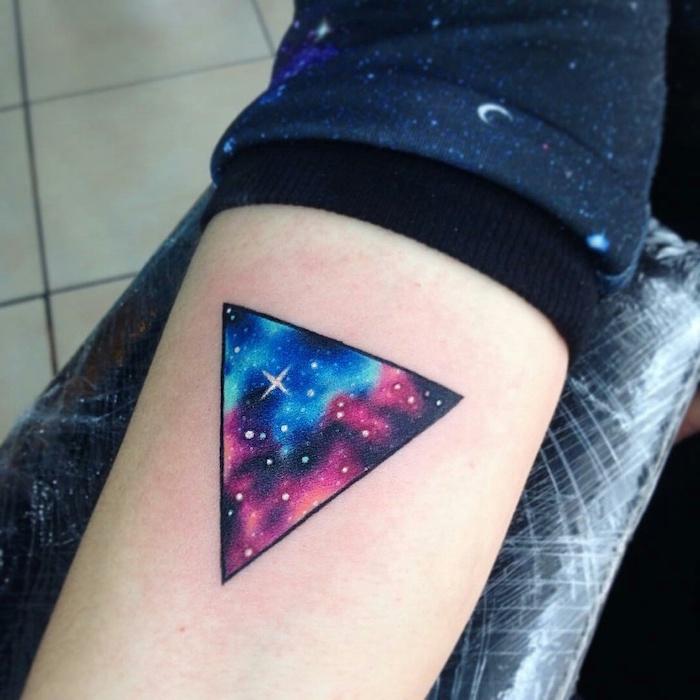 forearm geometrical triangle tattoo, milky way tattoo, pink blue and purple galaxy with stars inside the triangle