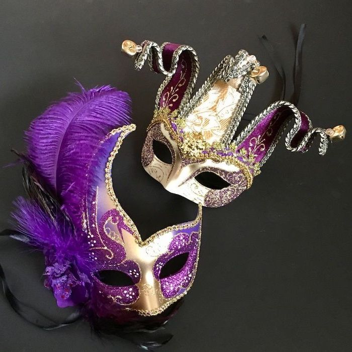 two gold masks, decorated with purple glitter, mens mardi gras masks, bells at the end, purple feathers