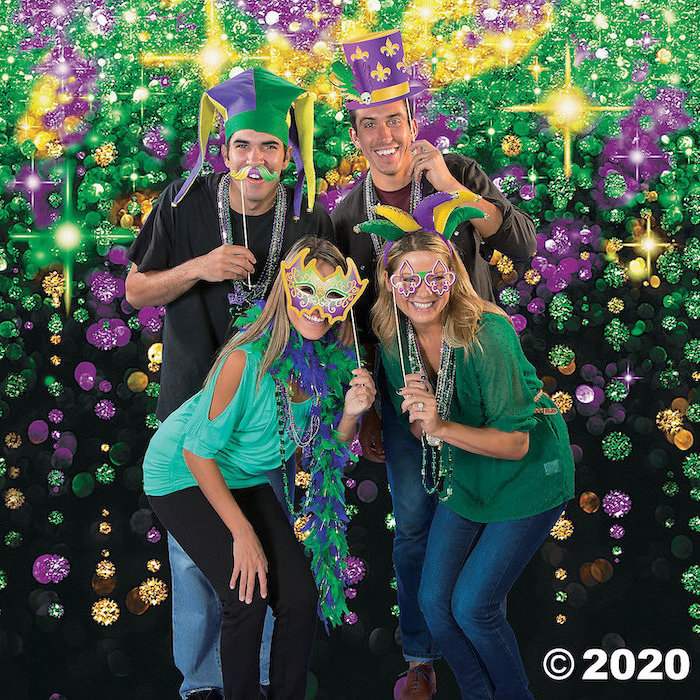 two men and two women posing for a photograph, mens mardi gras masks, wearing different masks in purple gold and green