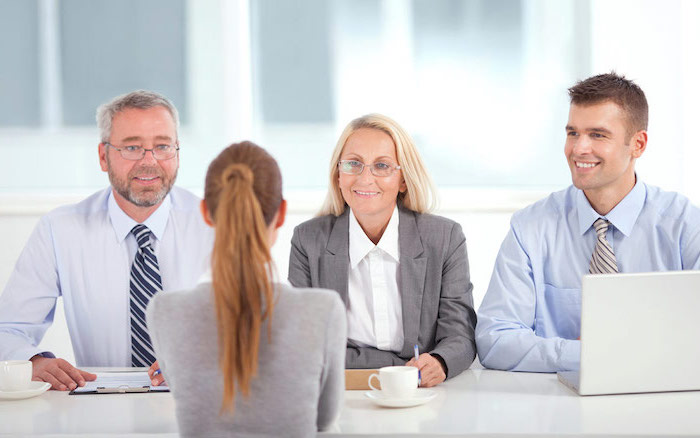 on woman and two men, dressed in business attire, sitting across from a blonde woman, job interview