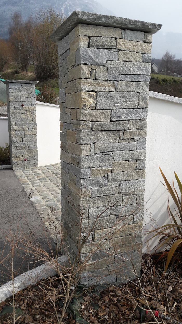 two large poles, made of stone, on both sides of a driveway, natural stone and reclaimed setts, small garden on the side