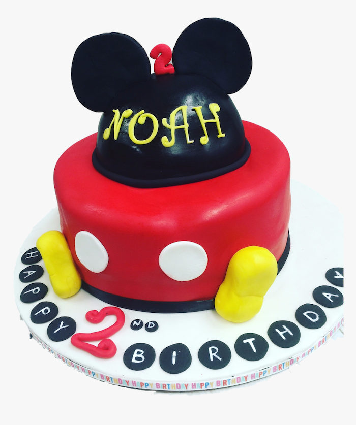 one tier cake, covered with black and red fondant, placed on white cake tray, mickey mouse cake pan